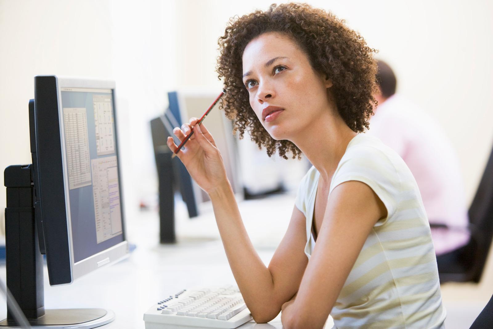Woman in computer room thinking | OWLLytics